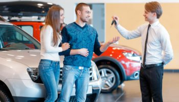 Buying their first car together. Handsome smiling sales consultant in car dealership gives keys from new car to young couple
